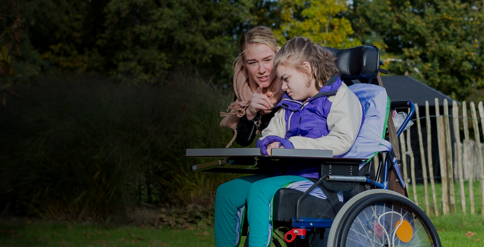 A disabled girl in a wheelchair relaxing outside together with a care assistant